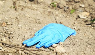 A forensic glove is located in the crime scene after a U.S. Border Patrol kidnapped and assaulted three immigrants from Honduras Thursday March 13, 2014, in Mission, Texas. Esteban Manzanares shot himself in the head killing himself before FBI agents entered his apartment. (AP Photo/The Monitor, Gabe Hernandez)
