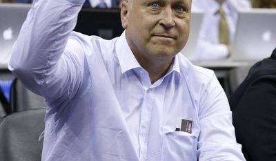 Baseball Hall of Famer Cal Ripken Jr. waves to fans as he watches an NBA basketball game between the Orlando Magic and the Washington Wizards in Orlando, Fla., Friday, March 14, 2014. (AP Photo/John Raoux)