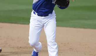 Oakland Athletics' Billy Burns (19) is forced out at second as Kansas City Royals' Christian Colon throws to first to complete a double play during the sixth inning of a spring exhibition baseball game on Friday, March 14, 2014, in Surprise, Ariz. (AP Photo/Darron Cummings)