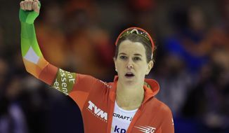 Ireen Wust of the Netherlands celebrates winning the women's 1500-meter speedskating race of the World Cup final at Thialf skating arena in Heerenveen, northern Netherlands, Friday, March 14, 2014. (AP Photo/Peter Dejong)