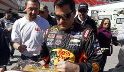 Driver Tony Stewart (14) signs autographs before practice for the NASCAR Sprint Cup series auto race at Bristol Motor Speedway on Friday, March 14, 2014, in Bristol, Tenn. (AP Photo/Wade Payne)