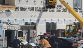 Emmett Township and LifeCare emergency personnel carry a victim of a scaffolding collapse to a waiting ambulance in Emmet Township, Mich., Friday, March 14, 2014. The scaffold collapse, at a hotel construction site, injured six workers. (AP Photo/The Enquirer,John Grap)  NO SALES