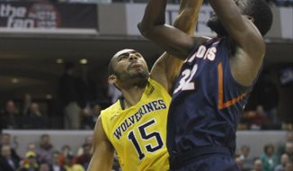 Michigan forward Jon Horford (15) blocks a shot by Illinois center Nnanna Egwu (32) in the first half of an NCAA college basketball game in the quarterfinals of the Big Ten Conference tournament Friday, March 14, 2014, in Indianapolis. (AP Photo/Kiichiro Sato)