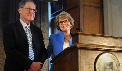 University of Michigan president Mary Sue Coleman holds onto her husband Kenneth as she speaks at a reception honoring her 12 years as president at the Michigan Union in Ann Arbor, Mich. Friday, March 14. (AP Photo/The Ann Arbor News, Brianne Bowen)