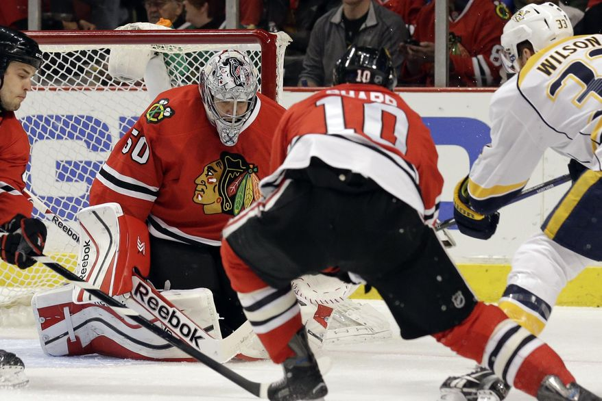 Chicago Blackhawks goalie Corey Crawford (50) saves the puck hit by Nashville Predators' Colin Wilson (33) during the first period of an NHL hockey game in Chicago, Friday, March 14, 2014. (AP Photo/Nam Y. Huh)