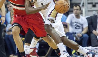 New Orleans Pelicans forward Tyreke Evans (1) dribbles around Portland Trail Blazers forward Nicolas Batum (88) in the first half of an NBA basketball game in New Orleans, Friday, March 14, 2014. (AP Photo/Scott Threlkeld)