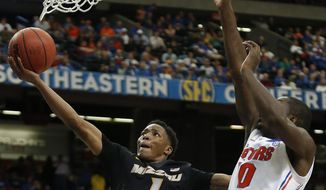 Missouri guard Wes Clark (1) shoots over Florida forward Dorian Finney-Smith (10) during the second half of an NCAA college basketball game in the quarterfinal round of the Southeastern Conference men's tournament, Friday, March 14, 2014, in Atlanta. (AP Photo/John Bazemore)