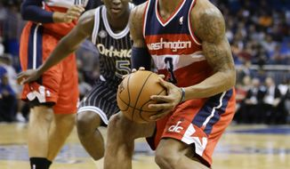 Washington Wizards guard Bradley Beal (3) looks to take a shot as Orlando Magic's Victor Oladipo (5) comes in to defend during the first half of an NBA basketball game in Orlando, Fla., Friday, March 14, 2014. (AP Photo/John Raoux)