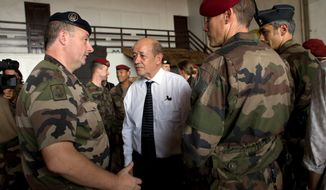 **FILE** French Defense Minister Jean-Yves Le Drian talks Jan. 2, 2014, with French soldiers from Operation Sangaris, at Mpoko Camp in Bangui, Central African Republic. France will broaden its military presence in Africa's turbulent Sahel region with specialized new outposts to better fight the terror threat from extremist groups such as al Qaeda, the defense minister said. (Associated Press)