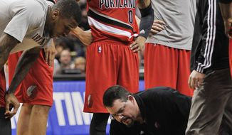 Portland Trail Blazers forward LaMarcus Aldridge (12) is helped by medical staff as teammates watch during the second half of an NBA basketball game against the San Antonio Spurs on Wednesday, March 12, 2014, in San Antonio. San Antonio won 103-90. (AP Photo/Darren Abate)