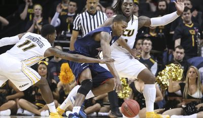 Richmond forward Terry Allen (15) drives against VCU forward Mo Alie-Cox (12), right, during the first half of an NCAA college basketball game in the quarterfinal round of the Atlantic 10 Conference tournament at the Barclays Center in New York, Friday, March 14, 2014. (AP Photo/John Minchillo)