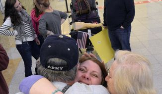 Lisa Bundy, foreground center, of Montgomery, Ala., hugs her father, Wayne Munsch, and friend Pat Creppel, both of New Orleans, upon returning to American soil, Friday, March 14, 2014, at Hartsfield Jackson Atlanta International Airport, in Atlanta. Lisa and daughter Nastia returned from Ukraine after finalizing Nastia's adoption there. (AP Photo/AL.com, Julie Bennett)
