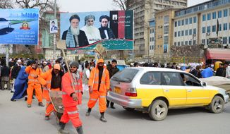Municipal workers in Kabul set about their daily routine as people rush to the nearby Afghan  market on March 13, 2014. Canada is looking to promote mining and business activity in Afghanistan as way build the country's moribund economy.  (AP Photo/The Canadian Press, Murray Brewster)
