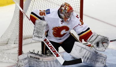 Calgary Flames goalie Joey MacDonald (35) makes a save in the first period of an NHL hockey game against the Dallas Stars, Friday, March 14, 2014, in Dallas. (AP Photo/Sharon Ellman)