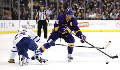 Los Angeles Kings' Anze Kopitar, right, of Slovenia, controls the puck against Toronto Maple Leafs' Carl Gunnarsson, of Sweden, during the second period of an NHL hockey game on Thursday, March 13, 2014, in Los Angeles. (AP Photo/Jae C. Hong)