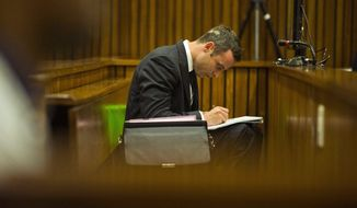 Oscar Pistorius writes notes as he sits in the dock during his trial in court in Pretoria, South Africa, Thursday, March 13, 2014. Pistorius is charged with the shooting death of  his girlfriend Reeva Steenkamp on Valentine's Day in 2013.  (AP Photo/Alet Pretorius, Pool)