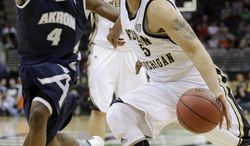 Western Michigan's David Brown (5) drives past Akron's Deji Ibitayo (4) during the first half of an NCAA college basketball game at the Mid-American Conference tournament Friday, March 14, 2014, in Cleveland. (AP Photo/Tony Dejak)