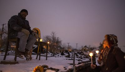 Sam Deniston, right, of Detroit, talks with Heidelberg Project artist and founder Tyree Guyton at a vigil at the site of the latest fire at the Heidelberg Project in Detroit, Thursday, March 13, 2014.  A March 7 fire destroyed a house covered in stuffed animals and dolls that was part of the Heidelberg Project. It was the latest casualty in a 10-month string of suspicious fires at houses that are part of the interactive outdoor art installation.   Guyton founded the Heidelberg Project on Detroit's east side in 1986 as a response to urban decay. (AP Photo/The Saginaw News, Katie Bailey) ALL LOCAL TV OUT; LOCAL TV INTERNET OUT