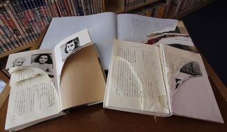 """In this Friday, Feb. 21, 2014 photo, ripped copies of Anne Frank's """"Diary of a Young Girl"""" and related books are shown at Shinjuku City Library in Tokyo. Japanese police have arrested a man for allegedly tearing pages out of books related to Frank at a Tokyo library. More than 300 books related to Frank have been found vandalized recently at libraries across Japan's capital. Tokyo police say the man, who was arrested Friday, March 14 sneaked into a library and ripped pages from 23 of the books on Feb. 5. Some of the ripped pages were found in a plastic bag at an unidentified house in Tokyo. (AP Photo/Koji Ueda)"""