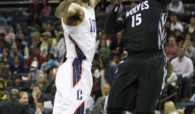 Minnesota Timberwolves forward Shabazz Muhammad, right, shoots over Charlotte Bobcats guard Chris Douglas-Roberts during the first half of an NBA basketball game in Charlotte, N.C., Friday, March 14, 2014. (AP Photo/Nell Redmond)