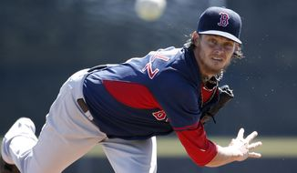 Boston Red Sox starting pitcher Clay Buchholz delivers a warm-up pitch before the start of a spring exhibition baseball game against the Toronto Blue Jays in Dunedin, Fla., Friday, March 14, 2014.  Buchholz allowed no runs on two hits with three strikeouts in four innings. (AP Photo/Kathy Willens)