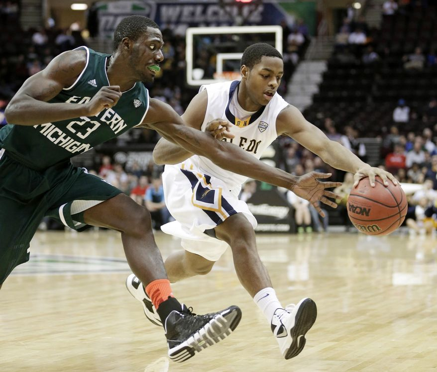 Eastern Michigan's Glenn Bryant, left, and Toledo's Jonathan Williams battle for a loose ball during the first half of an NCAA college basketball game at the Mid-American Conference tournament Friday, March 14, 2014, in Cleveland. (AP Photo/Tony Dejak)