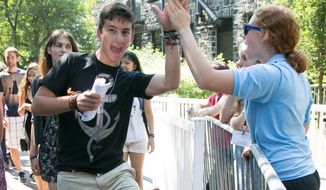 First-year students are welcomed to the Academic Quad with high fives. (Image: Facebook, Tufts University)