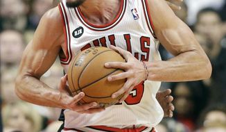 Chicago Bulls center Joakim Noah (13) works with the ball against Sacramento Kings forward Reggie Evans during the first half of an NBA basketball game in Chicago on Saturday, March 15, 2014. (AP Photo/Nam Y. Huh)