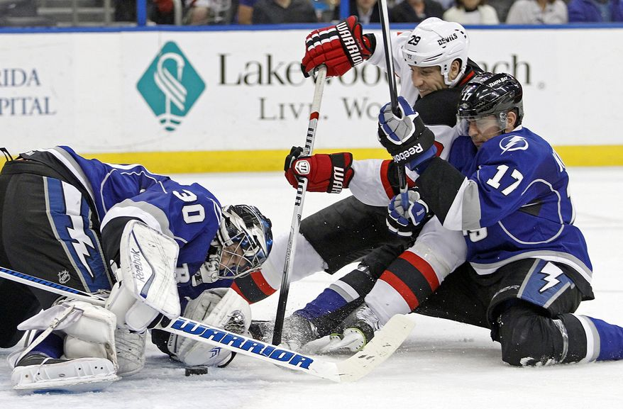 Tampa Bay Lightning goalie Ben Bishop (30) and center Alex Killorn (17) defend the goal from New Jersey Devils left wing Ryane Clowe (29) during the first period of an NHL hockey game Saturday, March 15, 2014, in Tampa, Fla. (AP Photo/Brian Blanco)