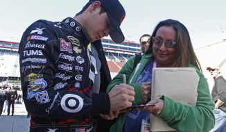 Driver Kyle Larson (42) signs an autograph after qualifying for the NASCAR Nationwide series auto race at Bristol Motor Speedway on Saturday, March 15, 2014, in Bristol, Tenn. Larson will start from the pole position. (AP Photo/Wade Payne)