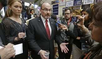 Gubernatorial candidate Tim Donnelly, center, gestures while speaking with reporters at the California Republican Party 2014 Spring Convention Saturday, March 15, 2014, in Burlingame, Calif. (AP Photo/Ben Margot)