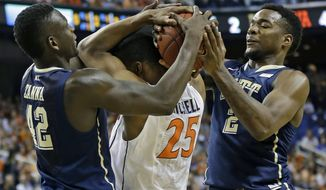 Virginia's Akil Mitchell (25) is tied up by Pittsburgh's Michael Young (2) and Talib Zanna (42) during the first half of an NCAA college basketball game in the semifinals at the Atlantic Coast Conference tournament in Greensboro, N.C., Saturday, March 15, 2014. (AP Photo/Gerry Broome)