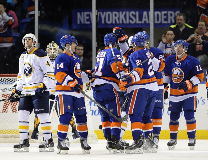 New York Islanders' Frans Nielsen (51) is congratulated by teammates as Buffalo Sabres' Jamie McBain (4) after Nielsen scored in the first period of an NHL hockey game on Saturday, March 15, 2014, in Uniondale, N.Y. (AP Photo/Kathy Kmonicek)