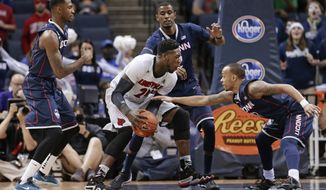 Louisville forward Montrezl Harrell (24) drives between Connecticut's Phillip Nolan, left, DeAndre Daniels, center, and Shabazz Napier, right, during the first half of an NCAA college basketball game in the finals of the American Athletic Conference men's tournament Saturday, March 15, 2014, in Memphis, Tenn. (AP Photo/Mark Humphrey)