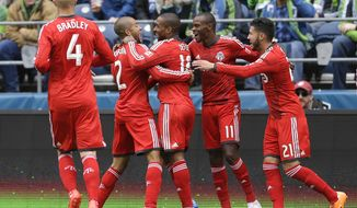 Toronto FC's Jermain Defoe, center, celebrates with teammates Michael Bradley (4), Justin Morrow (2), Jackson (11) and Jonathan Osorio (21) after scoring his first of two goals in the first half of an MLS soccer match against the Seattle Sounders, Saturday, March 15, 2014, in Seattle. (AP Photo/Ted S. Warren)