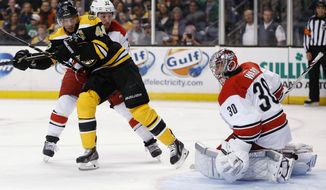 Boston Bruins' David Krejci (46) looks for the rebound after his shot on Carolina Hurricanes' Cam Ward (30) as Justin Faulk (27) defends in the second period of an NHL hockey game in Boston, Saturday, March 15, 2014. (AP Photo/Michael Dwyer)