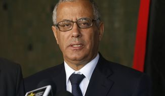 FILE - In this Tuesday, Oct. 8, 2013 file photo, then Libyan Prime Minister Ali Zidan speaks to the media during a press conference in Rabat, Morocco. Zidan, ousted prime minister, has left the country despite a ban on travel, hours after parliament removed him from office in a no-confidence vote. In Malta, Libya's Prime Minister Joseph Muscat told state-owned television that Zidan had made a brief stop-over on the Mediterranean island late on Tuesday, March 11, 2014, before traveling on. (AP Photo/Abdeljalil Bounhar, File)