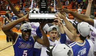 Tulsa players celebrate with the trophy after  their 69-60 win over  Louisiana Tech an NCAA college basketball game in the championship of the Conference USA tournament Saturday, March 15, 201,  in El Paso, Texas. (AP Photo/Victor Calzada)