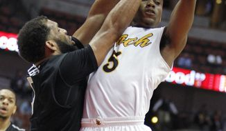 Long Beach State guard Mike Caffey, right, passes the ball away from Cal State Northridge forward J.J. Thomas during the first half of an NCAA college basketball game of the Big West Conference tournament in Anaheim, Calif., Friday, March 14, 2014. (AP Photo/Alex Gallardo)