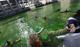 Elizabeth Saathoff left, and Scott Wrobel right, both of Chicago, photograph themselves with a smartphone after the Chicago River was dyed green ahead of the St. Patrick's Day parade in Chicago, Saturday, March 15, 2014. (AP Photo/ Paul Beaty)
