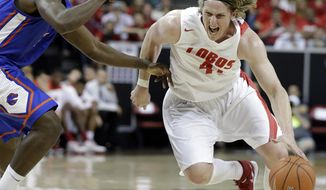 New Mexico's Cameron Bairstow drives past Boise State's Thomas Bropleh during the first half of an NCAA college basketball game in the semifinals of the Mountain West Conference men's tournament Friday, March 14, 2014, in Las Vegas. (AP Photo/Isaac Brekken)