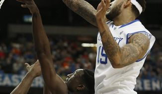 Kentucky forward Willie Cauley-Stein (15) hits the ball as Georgia forward Brandon Morris (31) shoots during the first half of an NCAA college basketball game in the semifinal round of the Southeastern Conference men's tournament, Saturday, March 15, 2014, in Atlanta. (AP Photo/John Bazemore)