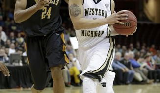 Western Michigan's David Brown, right, drives past Toledo's J.D. Weatherspoon (24) during the first half of an NCAA college basketball championship game at the Mid-American Conference tournament on Saturday, March 15, 2014, in Cleveland. (AP Photo/Tony Dejak)