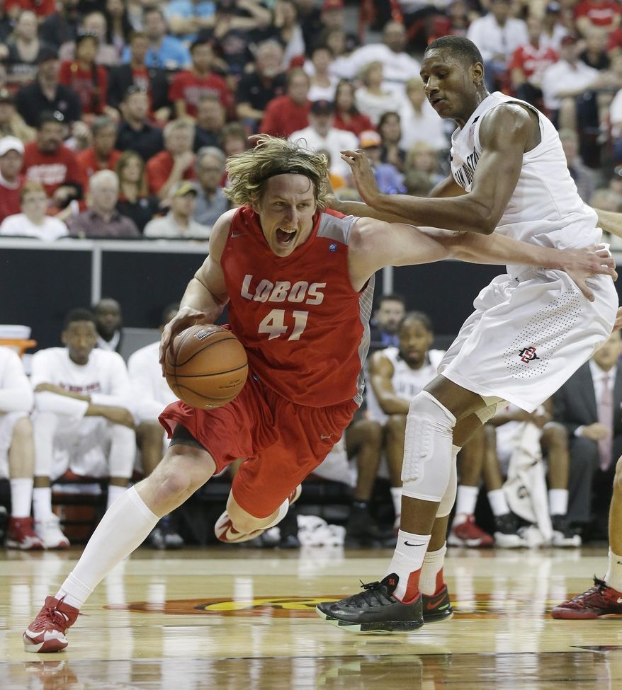 New Mexico's Cameron Bairstow, left, drives past San Diego State's Skylar Spencer during the first half of an NCAA college basketball game for the Mountain West Conference tournament championship on Saturday, March 15, 2014, in Las Vegas. (AP Photo/Isaac Brekken)