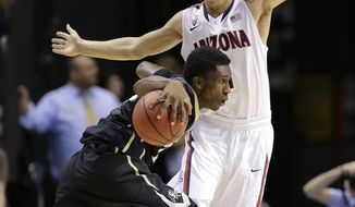 Colorado's John Hopkins drives against Arizona's Gabe York during the first half of an NCAA college basketball game in the semifinals of the Pac-12 Conference on Friday, March 14, 2014, in Las Vegas. (AP Photo/Julie Jacobson)