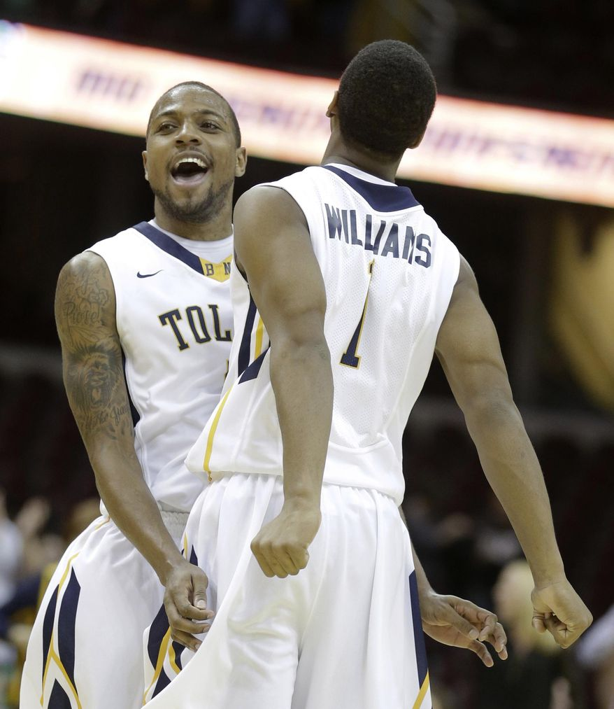 Toledo Rian Pearson, left, celebrates with Jonathan Williams after Toledo defeated Eastern Michigan 59-44 in an NCAA college basketball game at the Mid-American Conference tournament Friday, March 14, 2014, in Cleveland. (AP Photo/Tony Dejak)