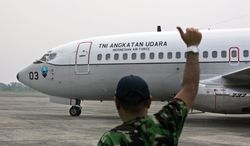 """A ground crew gives an 'OK' sign to the pilots of an Indonesian Air Force Boeing 737 """"Surveiller"""" of the 5th Air Squadron """"Black Mermaids"""" as they prepare to take off  for a search operation for the missing Malaysia Airlines jetliner MH370, at Suwondo Air base in Medan, North Sumatra, Indonesia, Saturday, March 15, 2014. The Malaysian passenger jet missing for more than a week had its communications deliberately disabled and its last signal came about seven and a half hours after takeoff, meaning it could have ended up as far as Kazakhstan or deep in the southern Indian Ocean, Malaysia's Prime Minister Najib Razak said Saturday. (AP Photo/Binsar Bakkara)"""