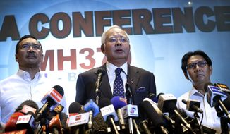 Malaysian Prime Minister Najib Razak, center, Malaysia's Minister for Transport Hishamuddin Hussein, left, and director general of the Malaysian Department of Civil Aviation, Azharuddin Abdul Rahman, delivers a statement to the media regarding the missing Malaysia Airlines jetliner MH370, Saturday, March 15, 2014 in Sepang, Malaysia. Najib said Saturday that investigators believe the missing Malaysian airliner's communications were deliberately disabled, that it turned back from its flight to Beijing and flew for more than seven hours. (AP Photo/Wong Maye-E)