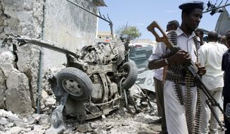 A Somali soldier walks near the wreckage of a car bomb that went off near the gate of one of Mogadishu's most popular hotels. Saturday, March, 15, 2014, A Somali police officer says a suicide car bomber accidentally detonated his explosives near a popular hotel in the Somali capital. Capt. Mohamed Hussein said the bomber appeared to have prematurely detonated his explosives-laden car Saturday as he tried to park near a hotel. No others were hurt or killed in the blast. (AP Photo/Farah Abdi Warsameh)