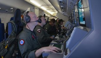 In this photo provided by the U.S. Navy, crew members on board an aircraft P-8A Poseidon assist in search-and-rescue operations for Malaysia Airlines flight MH370 in the Indian Ocean on March 16, 2014. (Associated Press)